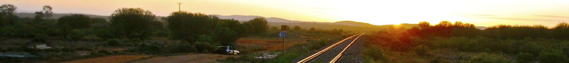 rail track heading towards sunset and distant future destination